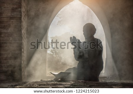 Silhouette of muslim man having worship and praying for fasting and Eid of Islam culture in old mosque with lighting and smoke background