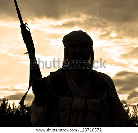 Silhouette of muslim rebel with rifle