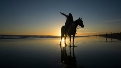 Silhouette of Muslim women who are riding horses on the beach with the atmosphere of the sunset