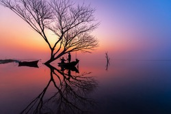 Silhouette of Myanmar fisherman on wooden boat .