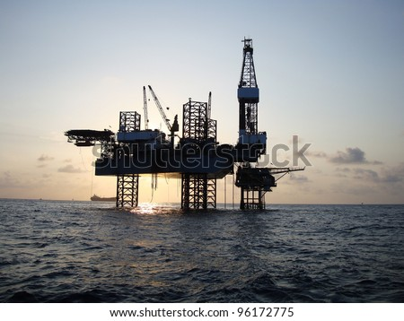Silhouette of Offshore Jack Up Rig in The Middle of The Sea at Sunset Time #96172775