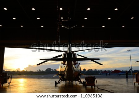 silhouette of offshore oil rig  helicopter in the hangar next to runway with sunrise background .