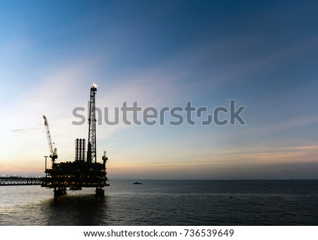 Silhouette of offshore production platforms connected with bridge during sunset at oilfield #736539649