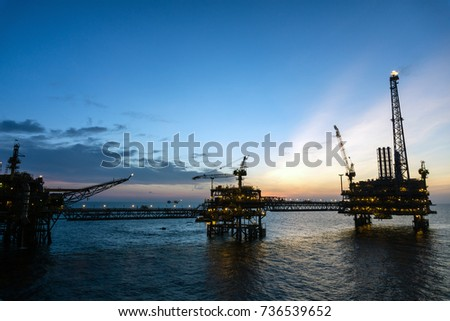 Silhouette of offshore production platforms connected with bridge during sunset at oilfield #736539652