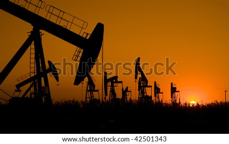 Silhouette of oil field with sunset