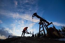 Silhouette of oil man in work vest and helmet. Petroleum operator working in oil field with long stroke balanced beam petroleum pump jack under beautiful sky. Concept of petroleum industry.