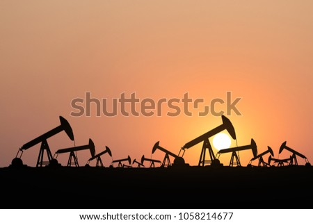 Silhouette of oil pump oil rig energy industrial machine for petroleum at sunset background.
