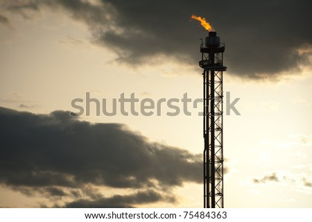 silhouette of oil refinery tower at sunset