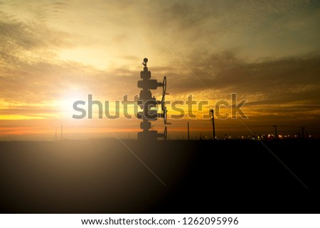 Silhouette of oil well manifold in the oilfield at sunset