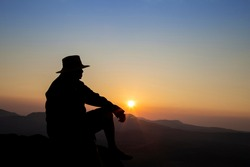 Silhouette of old man sitting on mountain peak during sunrise, man enjoying with nature view, landscape