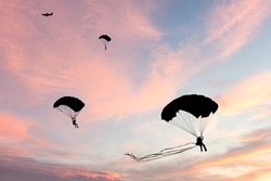 Silhouette of parachute and airplane on sunset background