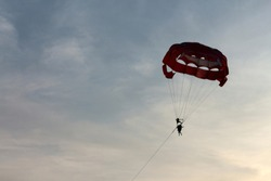 Silhouette of parachute (Parasailing) on sunset (sunrise) blue sky with clouds background