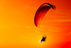 Silhouette of paraglider flying in the evening sky with sunset.