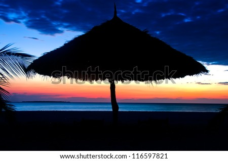 Silhouette of Parasol on a the Beach over Sunset with cloudy sky
