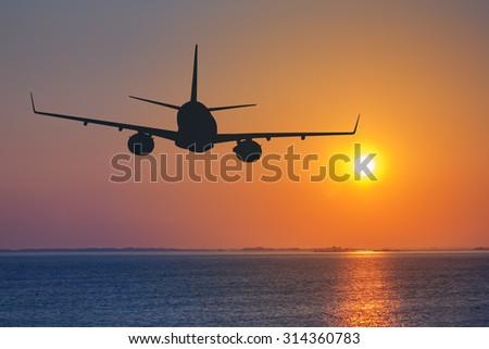 Silhouette of passenger airplane flying on sunset - Shutterstock ID 314360783