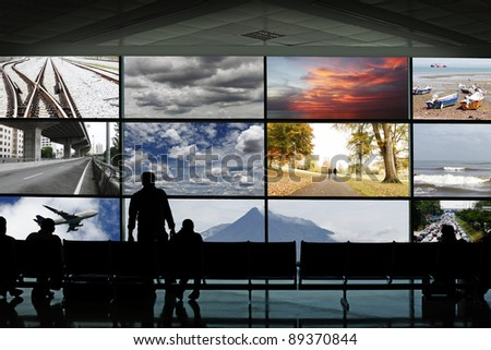 Silhouette of passengers at a waiting lounge in a transportation hub facing an advertisement panel frames showing various seasonal landscape and mode of transportation.