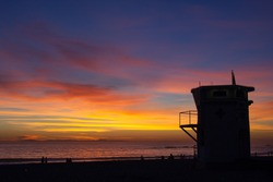 silhouette of people and lifeguard station watching a sunset over Laguna beach, California