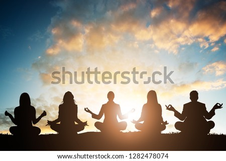 Silhouette Of People Doing Yoga Against Sky During Early Morning