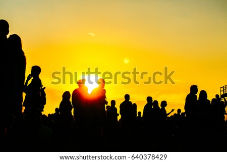 Silhouette of people in sunset on holiday. summer lifestyle. Colorful warm yellow toning. Recreation in park nature. Music Festival on outdoor