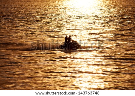 Silhouette of people on jet-ski against the sunset at sea - stock photo