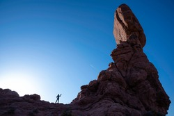 Silhouette of photographer and balanced rock in Arches national Park, Utah, USA. Spring time.