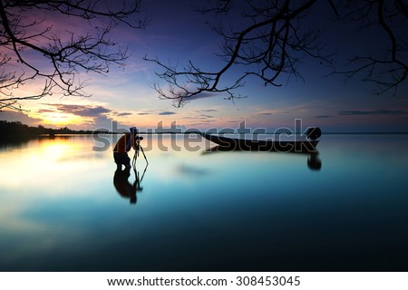 Silhouette of photographer looking to the boat near the beach when the sun goes down with branches tree border. Nature Photography