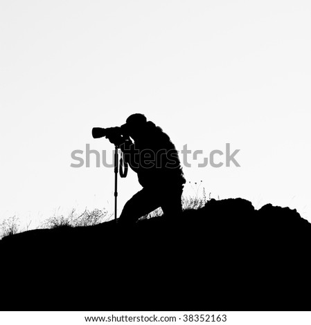 Silhouette of photographer on the hill with white background.