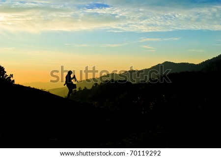 Silhouette of photographer on the mountain over the twilight sky