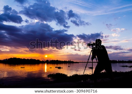 silhouette of photographer taking photo at sunset beside the river