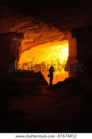 Silhouette of photographer taking photo in a cave (King Solomon Quarries a.k.a. Zedekiah's Cave in Jerusalem, Israel)
