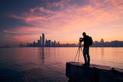 Silhouette of photographer with tripod. Young man photographing urban skyline. Abu Dhabi at dawn, United Arab Emirates