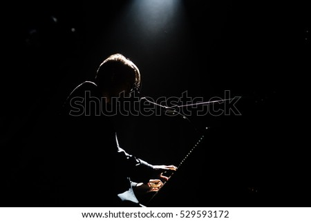 Silhouette of pianist in dark