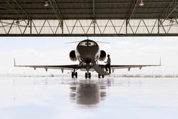 Silhouette of pilot boarding private jet in hangar