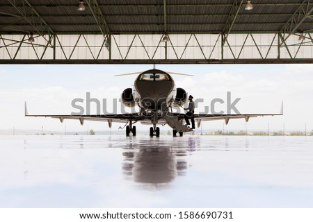 Silhouette of pilot boarding private jet in hangar