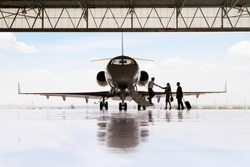 Silhouette of pilot greeting businessman and businesswoman boarding private jet in hangar