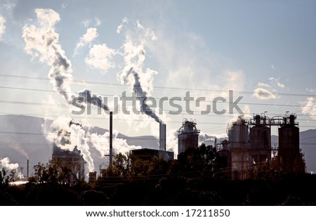 Silhouette of polluting gases steam and smoke coming from industrial site