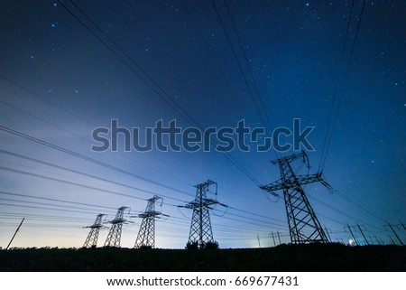 Silhouette of power lines on the background of beautiful starry sky at night.  #669677431