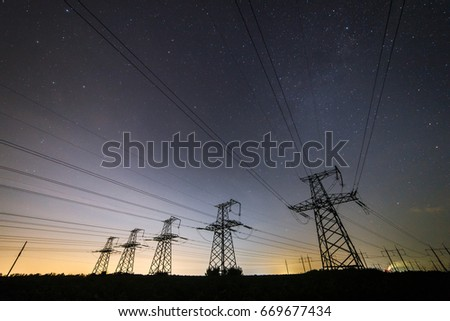 Silhouette of power lines on the background of beautiful starry sky at night.  #669677434