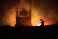 Silhouette of praying man with blurred mosque building on toned foggy background. Ramadan Kareem background. Muslim Eid holiday decoration. Praying people religion concept. Selective focus