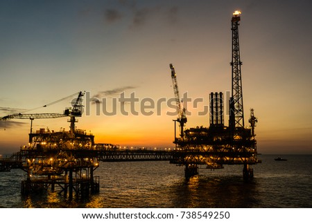 Silhouette of production platforms connected with a bridge during sunset at the oilfield #738549250