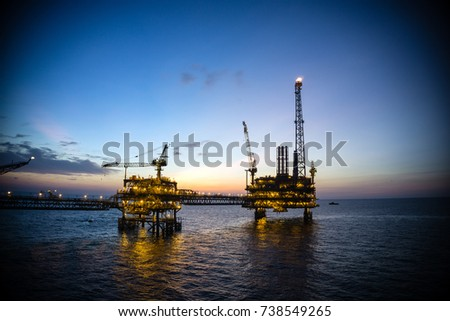 Silhouette of production platforms connected with a bridge during sunset at the oilfield #738549265