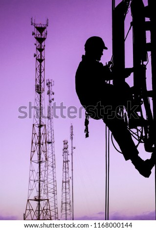Silhouette of professional industrial climber in helmet and uniform works at height for instaling communication equipment and antenna and telecommunication towers with sunset sky as background. Risky #1168000144
