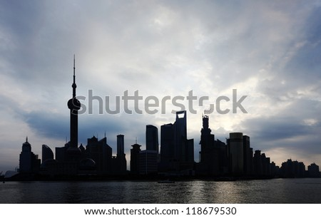 Silhouette of Pudong Financial District in Shanghai city, China on a dramatic morning cloudy sky.