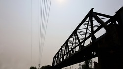 Silhouette of railway bridge. The iron bridge across the river on the background is cable and the sky with the afternoon sun shining with copy space. Selective focus