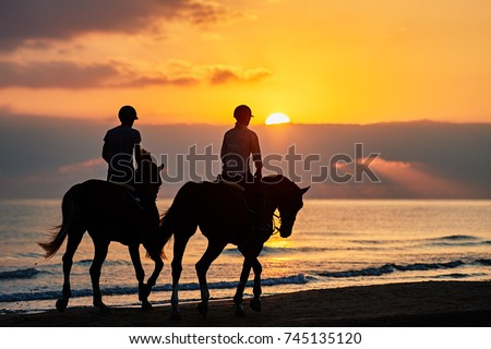Silhouette of riders exercising horses on the beach at sunrise