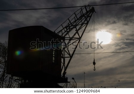 silhouette of river crane against the sun on a cloudy day #1249009684