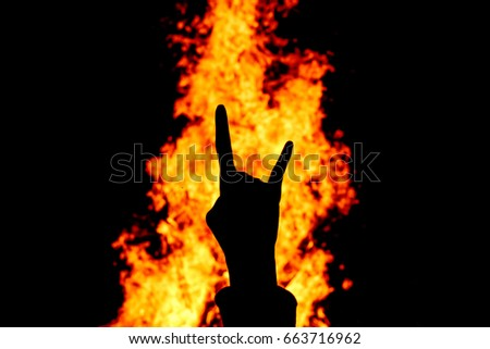 Silhouette of Rock and Roll hand sign against the fire background. #663716962