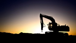 Silhouette of rock breaker with hydraulic  hammer at sunset in oilfield