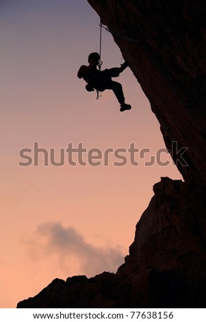 Silhouette of rock climber against sky background at sunset