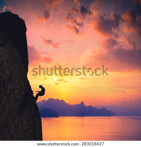 Silhouette of rock climber against sunset over the sea background